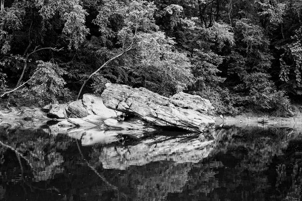 Black and white landscape photograph of large boulders reflecting into the placid surface of a slow-moving river.