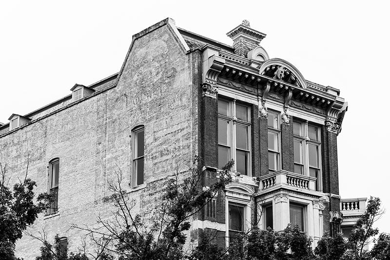 Black and white photograph of the historic Reuter Building on Alamo Plaza in San Antonio, Texas. In addition to it's impressive front facade, the brick side displays a beautiful multi-layered expanse of faded vintage ads. The Reuter Building is a four-story brick building with carved stone located on the corner of Crockett Street and Alamo Plaza. It was designed James Wahrenberger for William Reuter in 1891, and was operated as a saloon and ladies' parlor.
