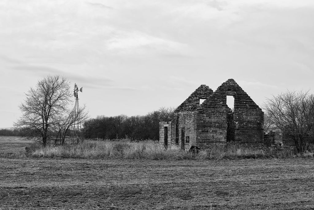 Black and white fine art photograph of an abandoned broken stone farmhouse with a windmill on the American prairie