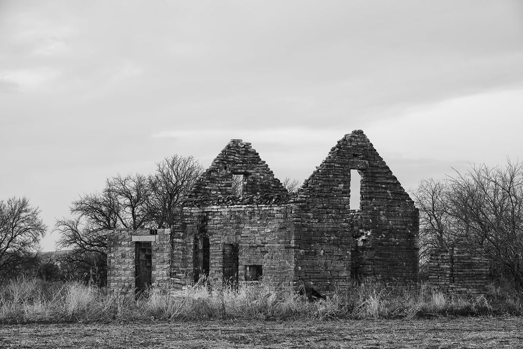 Black and white fine art photograph of an abandoned and collapsing stone farmhouse on the American prairie.