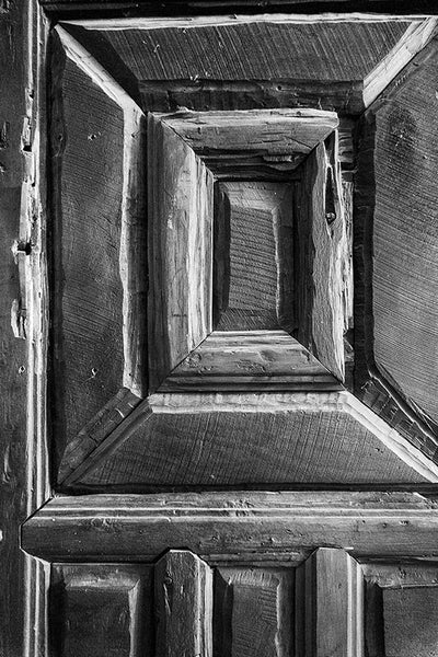 Black and white photograph of one of the rustic hand-carved wooden chapel doors at Mission San Jose in San Antonio, Texas.