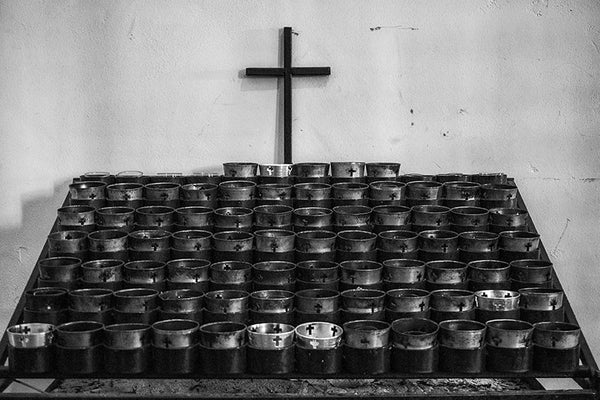 Black and white photograph of candles inside Mission San Jose, an old Spanish Catholic mission founded in 1720, with the church built in 1768. Along with the other San Antonio missions, Mission San Jose is a UNESCO World Heritage site.
