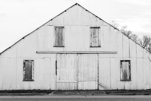 Black and white fine art photograph of an old shed painted white, with it's steep roofline forming a strong triangular composition with rectangles and lines.