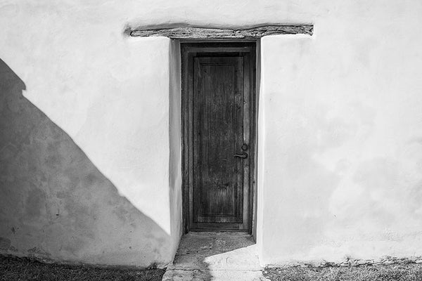 Black and white architectural photograph of a wooden door in the thick adobe wall of the old Spanish Mission San Juan Capistrano, which was established in San Antonio by Franciscans in 1731. The church was completed in 1756.