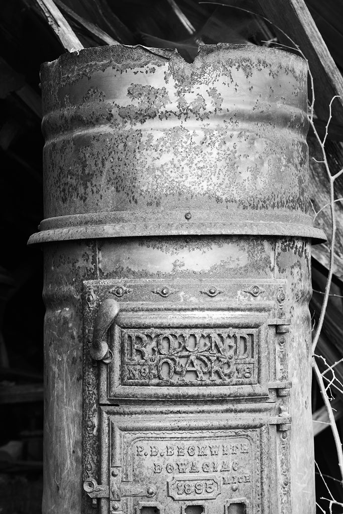 "Black and white fine art photograph of a rusty antique Round Oak stove discovered in a collapsing building in a small town. The words on the face of the stove read ""Round Oak No. 18, 1895, P.D. Beckwith, Dowagiac, Mich""."