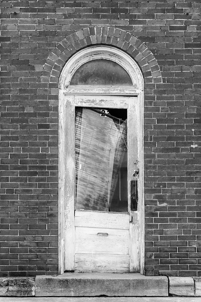 Black and white fine art photograph of an an old wooden door with a fanlight window in an abandoned storefront building in a small Midwestern town.