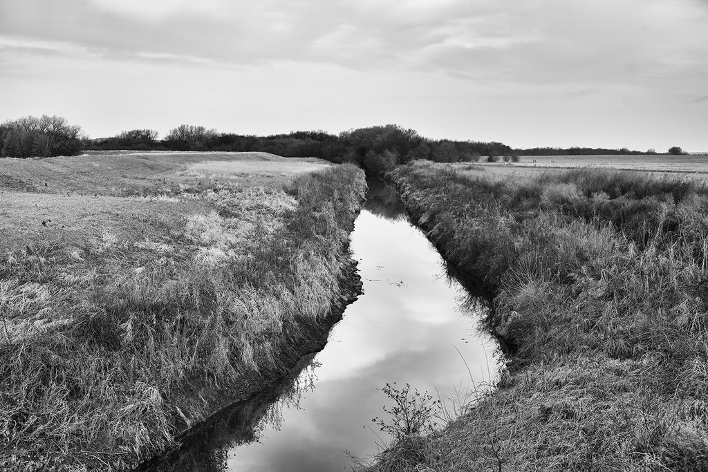 Black and white fine art photograph of a glassy creek winding through the undulant American prairie landscape