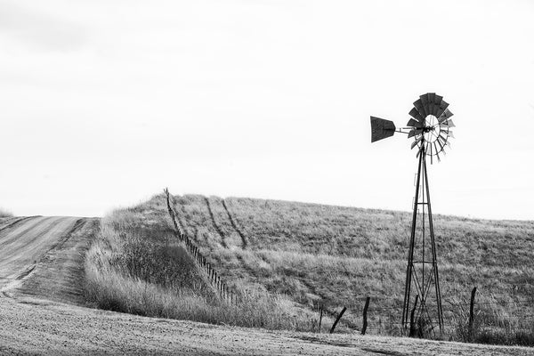 Black and white fine art photograph of the American prairie landscape featuring a dirt road and a windmill.