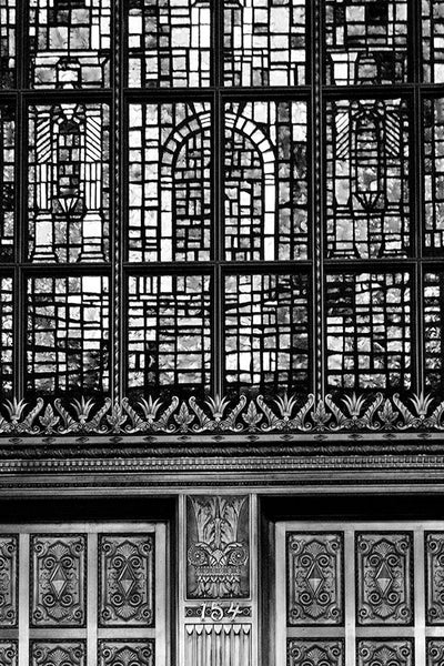 Black and white photograph of the old Alamo National Bank building built 1929 in San Antonio, Texas. This architectural detail photograph focuses on a section of the famous, massive stained glass window depiction of the Alamo, and some of the ornate metallic embellishment on the exterior of the building, which is now a hotel.