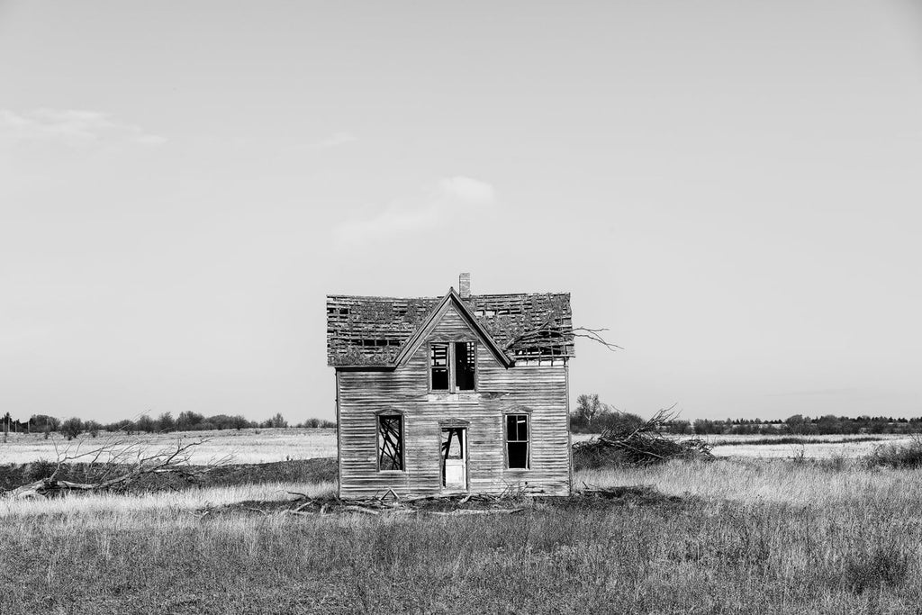 Black and white fine art photograph of an abandoned old wooden farmhouse on the American prairie.
