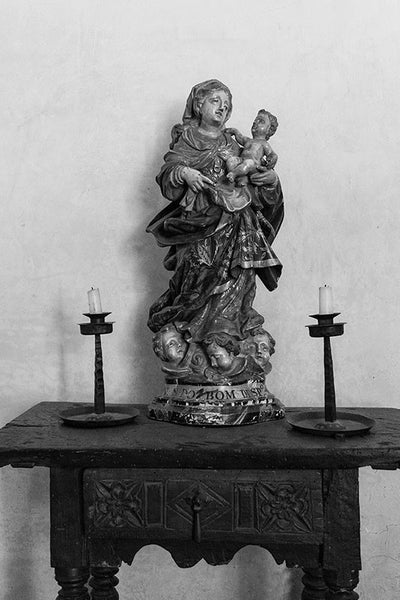 Black and white fine art photograph of the Madonna with Child on an antique Spanish table, between two unlit candles.