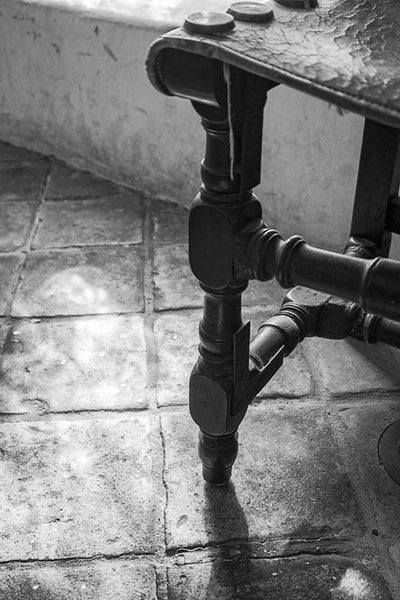 Black and white photograph of an antique Spanish chair on an old tile floor in the Spanish Governor's Palace in San Antonio, Texas.