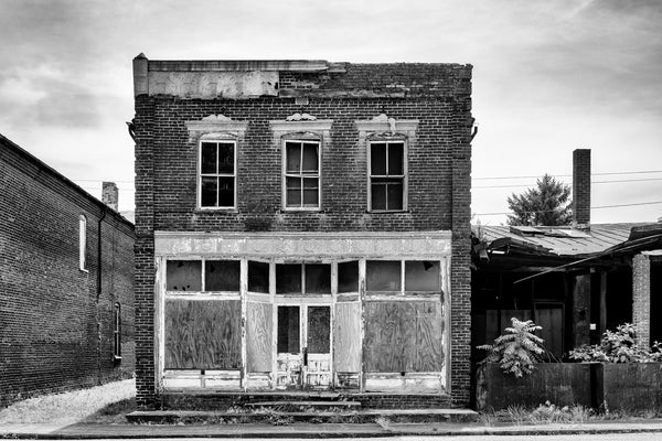 Black and white photograph of an empty storefront on the abandoned Main Street in the ghost town of Pamplin City, Virginia. The street is lined with 11 historic, vacant buildings.