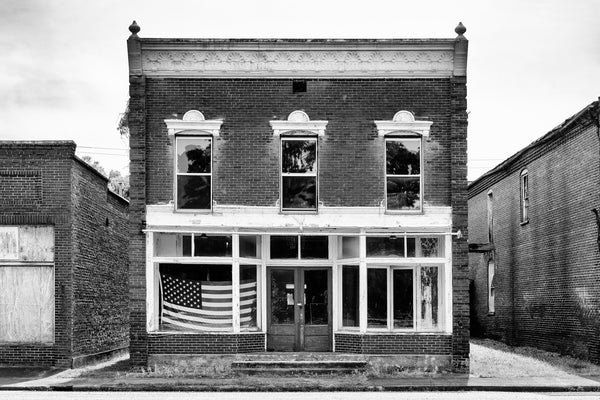 Black and white photograph of the front of an abandoned commercial building on the old Main Street in the ghost town of Pamplin City, Virginia. The street is lined with 11 historic and deserted buildings.