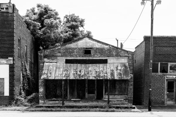 Black and white photograph of the long-abandoned Williams Hardware and Grocery in Pamplin City, Virginia. The entire Main Street of Pamplin City is abandoned. The old general store was owned by the Williams brothers for 30 years. Harry was also the local Postmaster. Woodrow was a professional baseball player with the Brooklyn Dodgers and Cincinnati Reds.