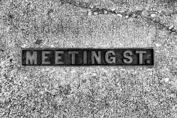 Black and white photograph of a Meeting Street sidewalk sign in historic Charleston, South Carolina.