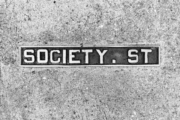 Black and white photograph of a Society Street sidewalk sign in historic Charleston, South Carolina.
