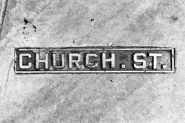 Black and white photograph of a Church Street sidewalk sign in historic Charleston, South Carolina.