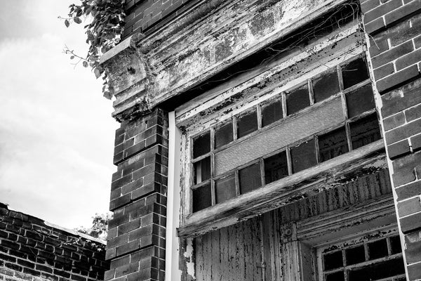 "Black and white photograph of frames of colored glass over the front door of an abandoned building in a small town. The portico is covered with cracked white paint. Over the door is a faded sign that says ""Estate."""