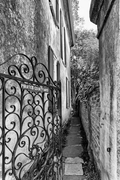Black and white photograph of an alley to the Pirate's Courtyard in the French Quarter section of Charleston, South Carolina.
