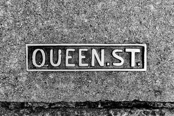 Black and white photograph of a Queen Street sidewalk sign placard in historic Charleston.