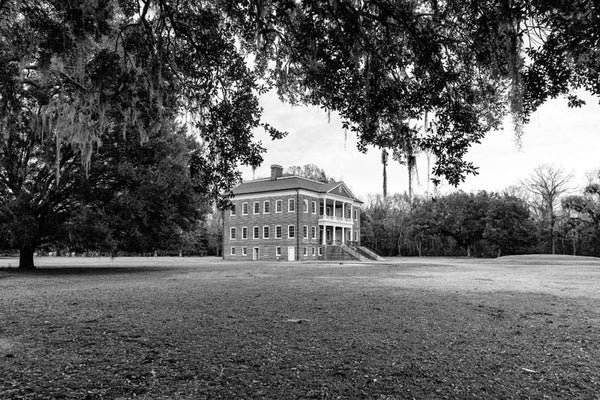 Black and white photograph of Drayton Hall, nine miles outside Charleston, South Carolina. Drayton Hall was built about 1740, and is the only South Carolina plantation home to survive the Revolutionary War and the Civil War intact. The house is now held in a state of preservation, maintained but not restored, which means that original paint, woodwork, and carved ceilings can still be seen.