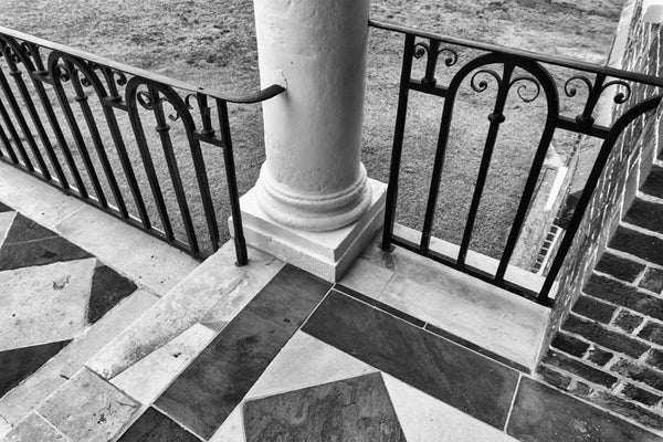 Black and white photograph of the portico at Drayton Hall, a 1740s English-style Palladian plantation home nine miles from Charleston on the Ashley River. Drayton Hall is the only old plantation home to survive both the revolutionary war and thUS Civil War intact. The home is now maintained in a preserved, not restored, condition.