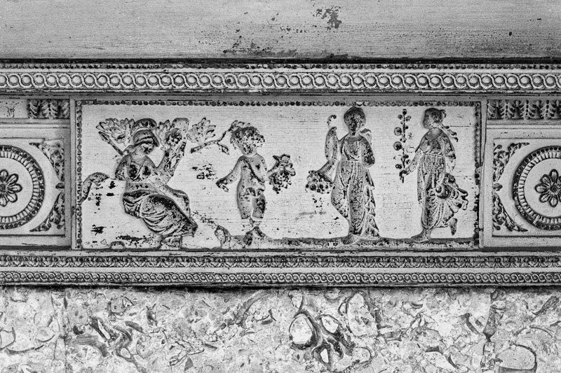 Black and white photograph of one of the scuffed antique fireplace mantels inside Drayton Hall, featuring classically-inspired figures.