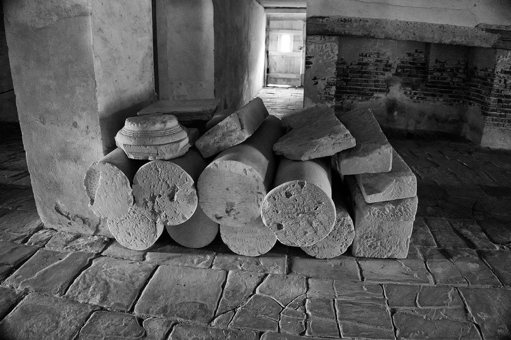 Black and white photograph of old stone columns stacked in the basement of Drayton Hall since at least the 1870s. Someone had them stacked there for storage, and they were never retrieved. Drayton Hall, built in the English Palladian style in 1738 near the bank of the Ashley River, was a grand country home for the wealthy Drayton family.