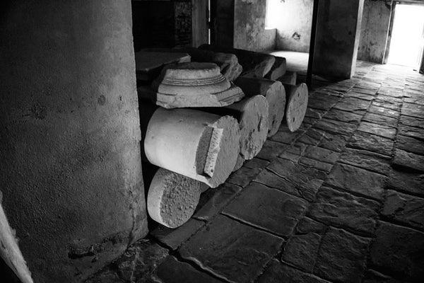 Black and white photograph of old stone columns stacked in the basement of Drayton Hall since at least the 1870s. Someone had them stacked here for storage, and they were never retrieved. Drayton Hall, built in the English Palladian style 1738 on the bank of the Ashley River is a grand southern home that predates the revolutionary war and the popular conception of an antebellum plantation home.