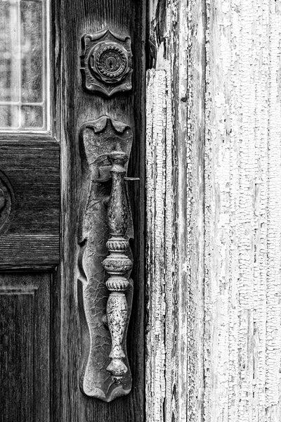 Black and white detail photograph of a fancy door handle on the antique door of an abandoned Main Street in the ghost town of Pamplin City, Virginia. The street is lined with 11 historic, vacant buildings.