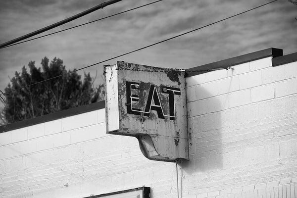 "Black and white photograph of a rusty vintage neon diner sign that says ""EAT"" in capital letters."