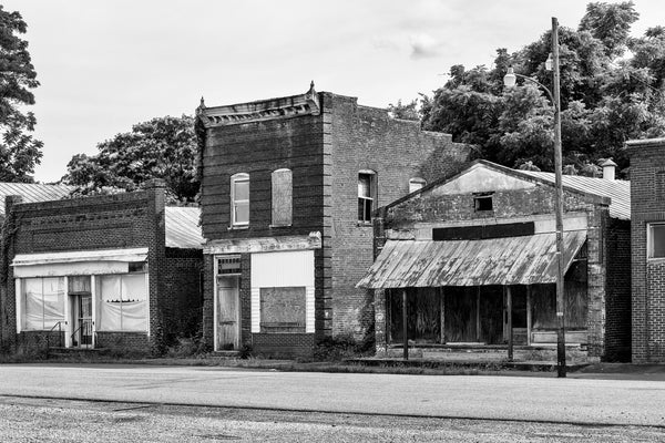 Black and white photograph of a row of abandoned storefronts along the deserted old Main Street in Pamplin City, Virginia.