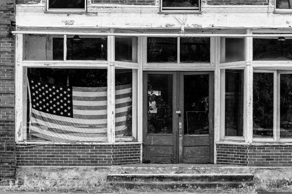Black and white photograph of an abandoned storefront with a US flag in the window on the deserted old Main Street in Pamplin City, Virginia.