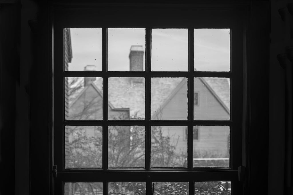 "Black and white photograph of the historic ""House of Seven Gables"" as seen through the window of the Hawthorne house. Both iconic New England mansions are hundreds of years old."