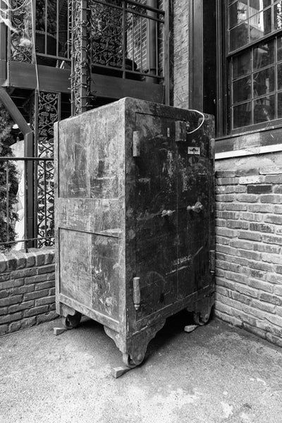 Black and white photograph of a big, rusty, antique safe sitting outside in Nashville's popular Printer's Alley entertainment district.