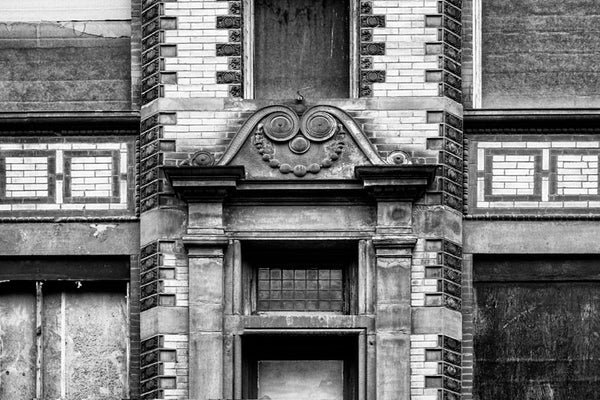 Black and white photograph of the tarnished architectural details and scrollwork motif on the front of an old building on Nashville's 3rd Avenue. Historically this part of Nashville was home to many furniture stores.