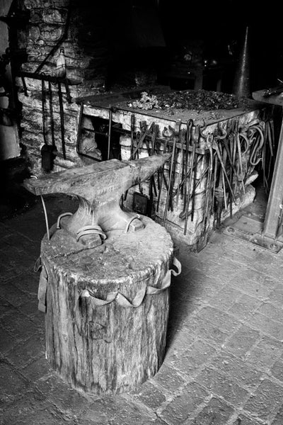 Black and white photograph of an anvil and tools in a blacksmith shop.