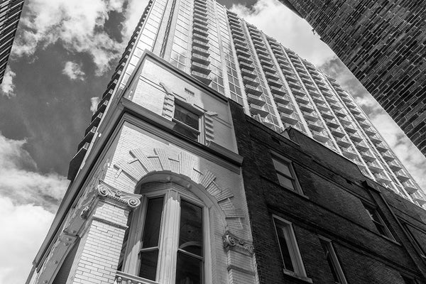 Black and white photograph looking up Nashville's historic Cohen building, dwarfed by modern skyscrapers, against a sunny Spring sky.