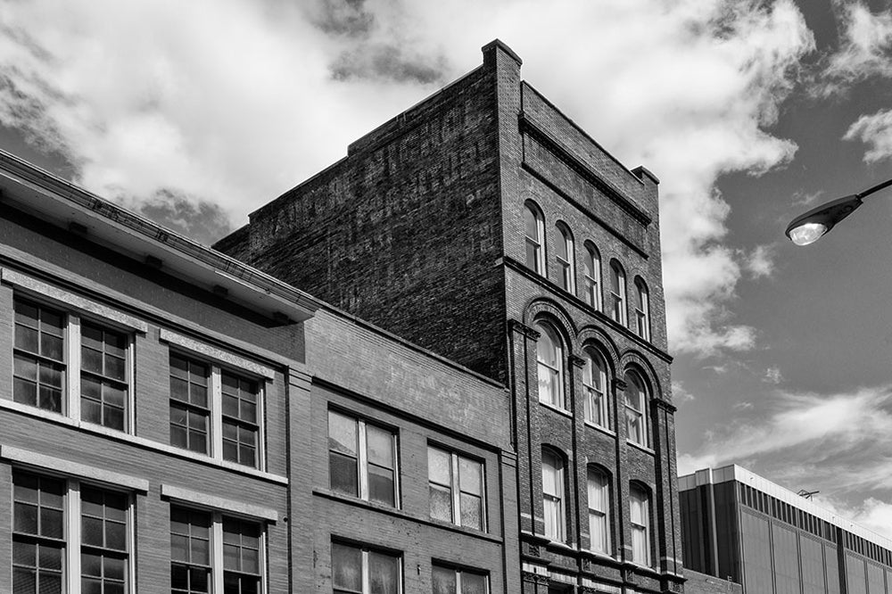 Black and white architectural photograph of a five-story brick building at 208 N. Third in Nashville, Tennessee. Constructed in 1900, this red brick gem features a beautifully fading painted ad for the Bradford Nichol Furniture company, which was open for business by at least 1870 at 25 and 27 North College Street in Nashville, according to a listing in The Masonic Record, published that year.