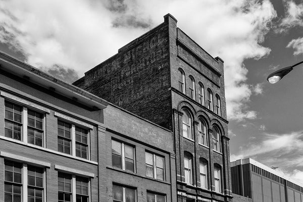 Black and white architectural photograph of a five-story brick building at 208 N. Third in Nashville, Tennessee. Constructed in 1900, this red brick gem features a beautifully fading painted ad for the Bradford Nichol Furniture company, which was open for business by at least 1870 at 25 and 27 College Street in Nashville, according to a listing in The Masonic Record, published that year.