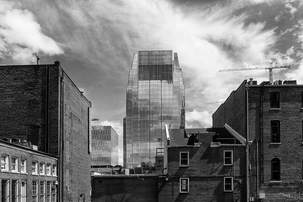 Black and white photograph of downtown Nashville featuring the Pinnacle Building, a modern glass office tower, framed by some of Nashville's older brick buildings and a few construction cranes.