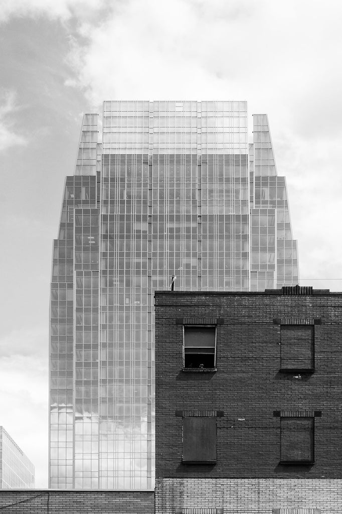 Black and white architectural photograph of Nashville's 2010 glass skyscraper called The Pinnacle at Symphony Place, towering over an old brick building probably dating to the 1890s-1900s. The Pinnacle at Symphony Place is 29 stories, 417 feet tall, and on sunny days like shown here, seems to become a mirage in the sky.