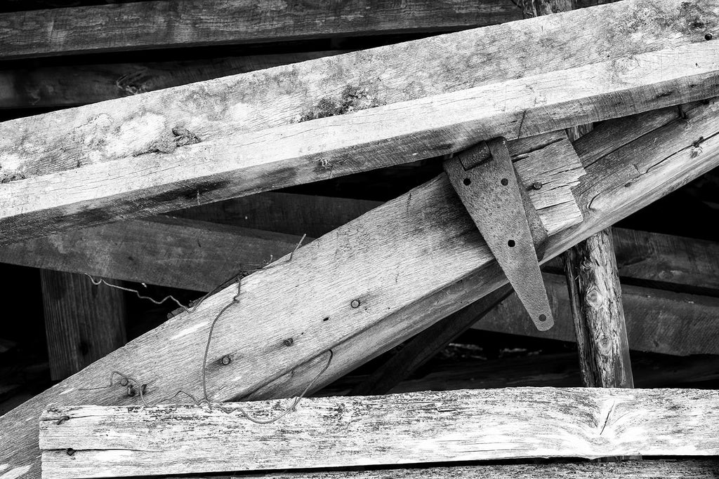 Black and white photograph of angled beams and a rusty metal hinge found in the shadows of a fallen old hay barn.