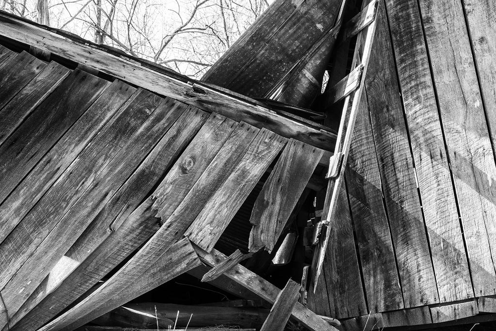 Black and white photograph of angled beams and wooden planks from an old collapsed hay barn.