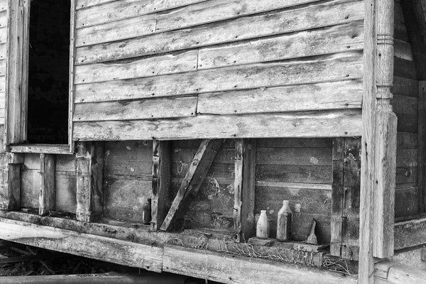 Black and white photograph of old bottles lined up on the side of an abandoned old farmhouse.