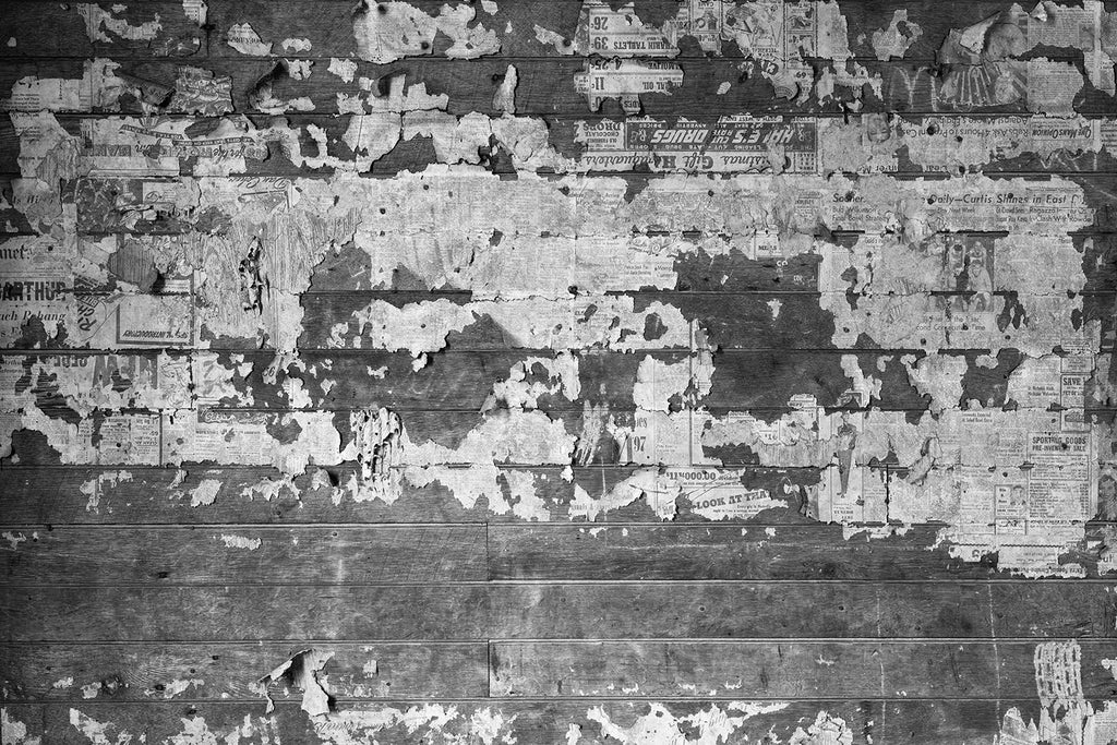 Black and white photograph of 70-year-old newspaper scraps pasted on the interior walls of an abandoned old farmhouse.