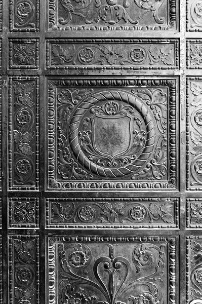 Black and white photograph of an ornately decorated bronze door in St. Augustine's old town neighborhood.