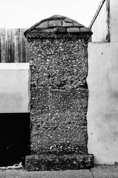 Black and white photograph of an old coquina wall in St. Augustine, Florida. It's the last remaining structure from that development. Coquina is a form of sedimentary rock made of mollusk shells that was mined and quarried for hundreds of years in the Caribbean and Florida.