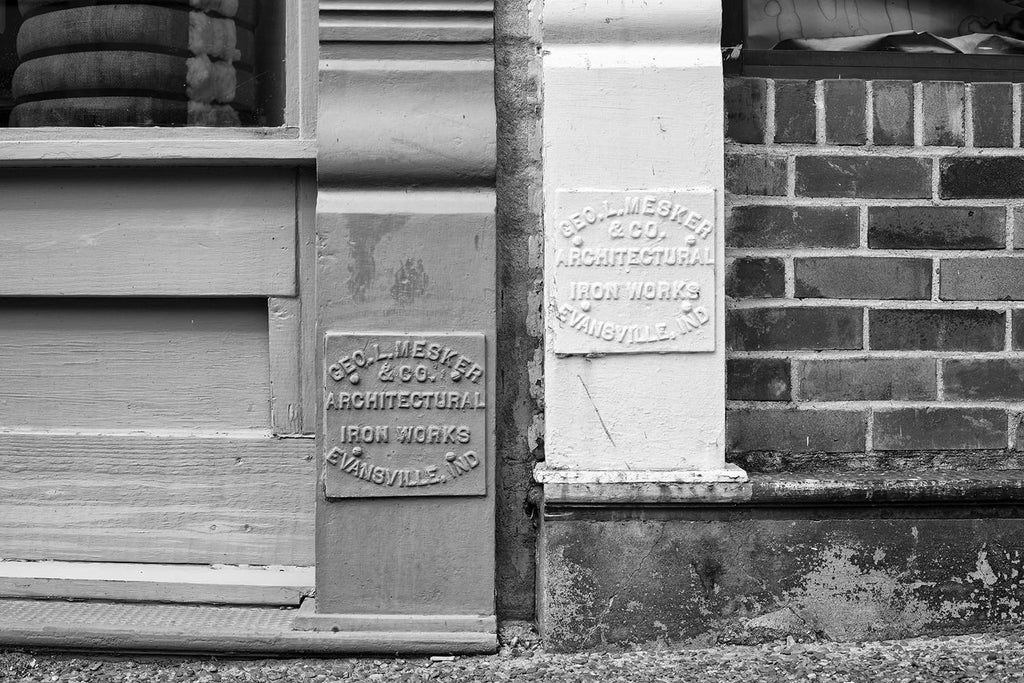 Black and white architectural detail photograph of two Mesker Iron Works identification panels found on historic storefront buildings in a small town.